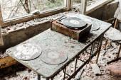 opuštěné vinylové rekordy na špinavém stole na pokoji