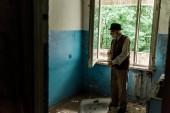 Fényképek szomorú magas rangú ember áll a sérült szobában