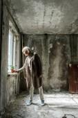 Fotografia donna in pensione mettendo piccola pianta in vaso in camera vuota vicino alla finestra