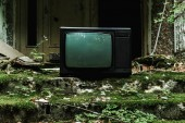 tv retrò su scale verdi con muffa vicino edificio