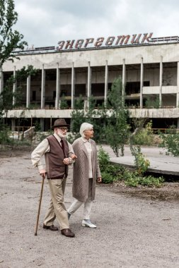 PRIPYAT, UKRAINE - AUGUST 15, 2019: senior couple walking near building with energetic lettering in chernobyl stock vector