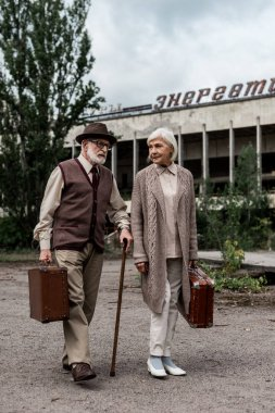 PRIPYAT, UKRAINE - AUGUST 15, 2019: retired couple with suitcases near building with energetic lettering in chernobyl stock vector