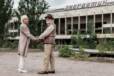 PRIPYAT, UKRAINE - AUGUST 15, 2019: retired couple holding hands near building with energetic lettering in chernobyl stock vector