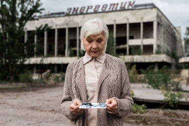PRIPYAT, UKRAINE - AUGUST 15, 2019: senior woman looking at photo near building with energetic lettering in chernobyl stock vector