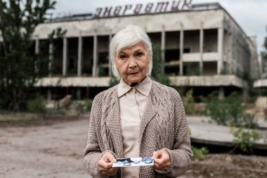 PRIPYAT, UKRAINE - AUGUST 15, 2019: senior woman holding photo near building with lettering in chernobyl stock vector