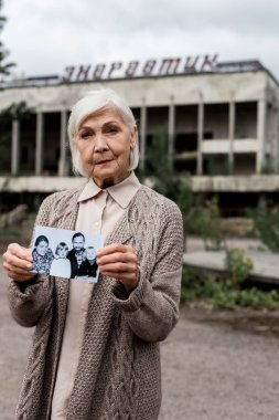 PRIPYAT, UKRAINE - AUGUST 15, 2019: senior woman holding photo near building with letters in chernobyl stock vector