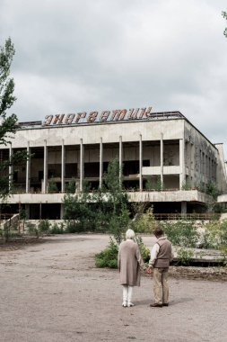 PRIPYAT, UKRAINE - AUGUST 15, 2019: back view of retired couple holding hands near building with energetic lettering in chernobyl stock vector