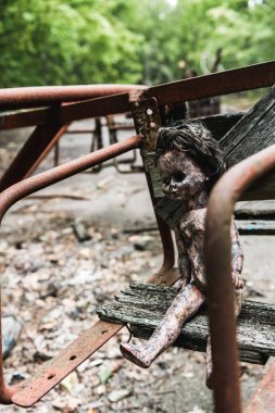 Selective focus of burnt baby doll on abandoned carousel in chernobyl stock vector