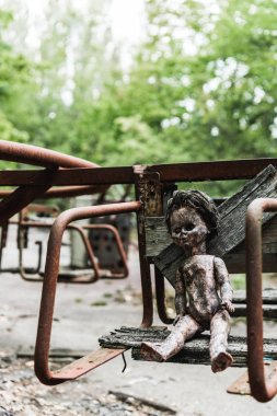 Selective focus of dirty baby doll on abandoned carousel in chernobyl stock vector