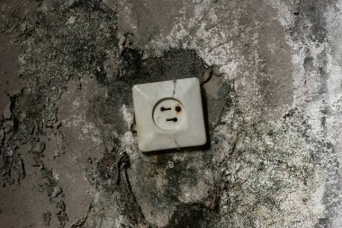 rusty power socket in damaged grey wall