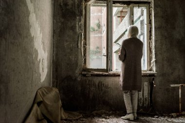back view of retired woman holding plant in empty room near windows