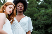 selective focus of attractive african american girl standing near redhead young woman