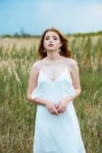 mladá rushlavka v bílých šatech v terénu