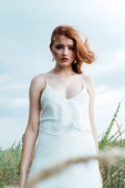 selektivní zaměření mladé červené ženy v bílých šatech na kameru