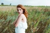 schöne Rothaarige Frau im weißen Kleid, die auf die Kamera schaut