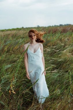 pretty young woman with red hair standing in dress