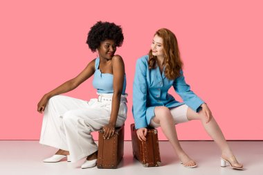 cheerful multicultural women sitting on suitcases on pink