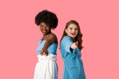 happy multicultural women pointing with fingers isolated on pink