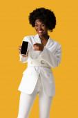 šťastná africko-americká dívka držící smartphone s prázdnou obrazovkou při ukazování prstem izolovaně na oranžovém