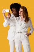 usmívající se multikulturní dívky, které si berou na oranžovou