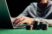 Fotografia vista ritagliata delluomo digitando su laptop vicino chip poker isolato su nero