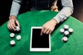 Fotografia vista superiore delluomo puntando con il dito al computer portatile con schermo bianco vicino a poker chips