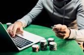 oříznutý pohled muže držáče pokeru a psaní na přenosný počítač izolovaný na černém