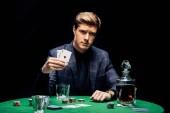 Kyjev, Ukrajina - 20. srpna 2019: selektivní zaměření pohledného muže držícího karty poblíž pokerových žetonů a alkoholických nápojů izolovaných na černém
