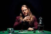 selektivní zaostření muže v brýlích blízko hrací karty izolované na černém
