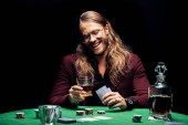 KYIV, UKRAINE - AUGUST 20, 2019: selective focus of happy bearded man in eye glasses near playing cards isolated on black