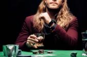Fotografie oříznutý pohled muže se sklenicí s whisky poblíž hrací karty izolované na černém