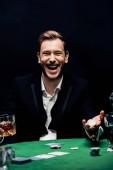 šťastný muž drží šťouchací karty a sklo s alkoholem izolované na černé