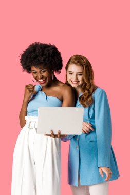 happy multicultural girls looking at laptop isolated on pink