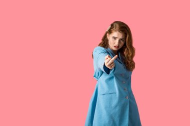 displeased redhead girl looking at camera and showing middle finger isolated on pink