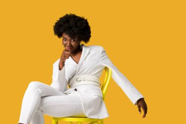Smiling african american woman sitting on yellow chair and pointing with finger isolated on orange stock vector