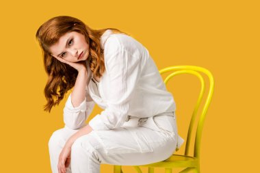 sad redhead girl sitting on yellow chair isolated on orange