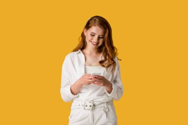 happy redhead girl using smartphone and smiling isolated on orange