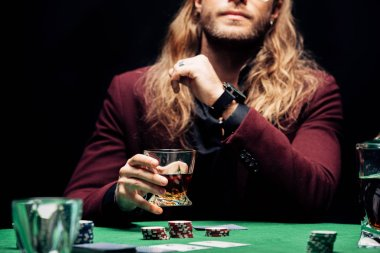 cropped view of man holding glass with whiskey near playing cards isolated on black