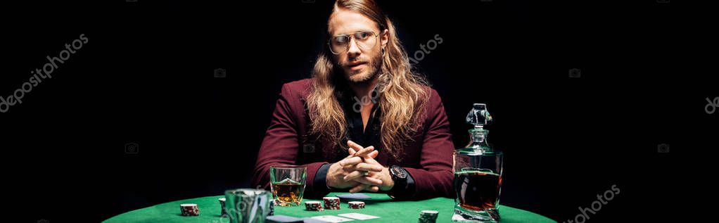 Panoramic shot of bearded man in eye glasses near playing cards isolated on black