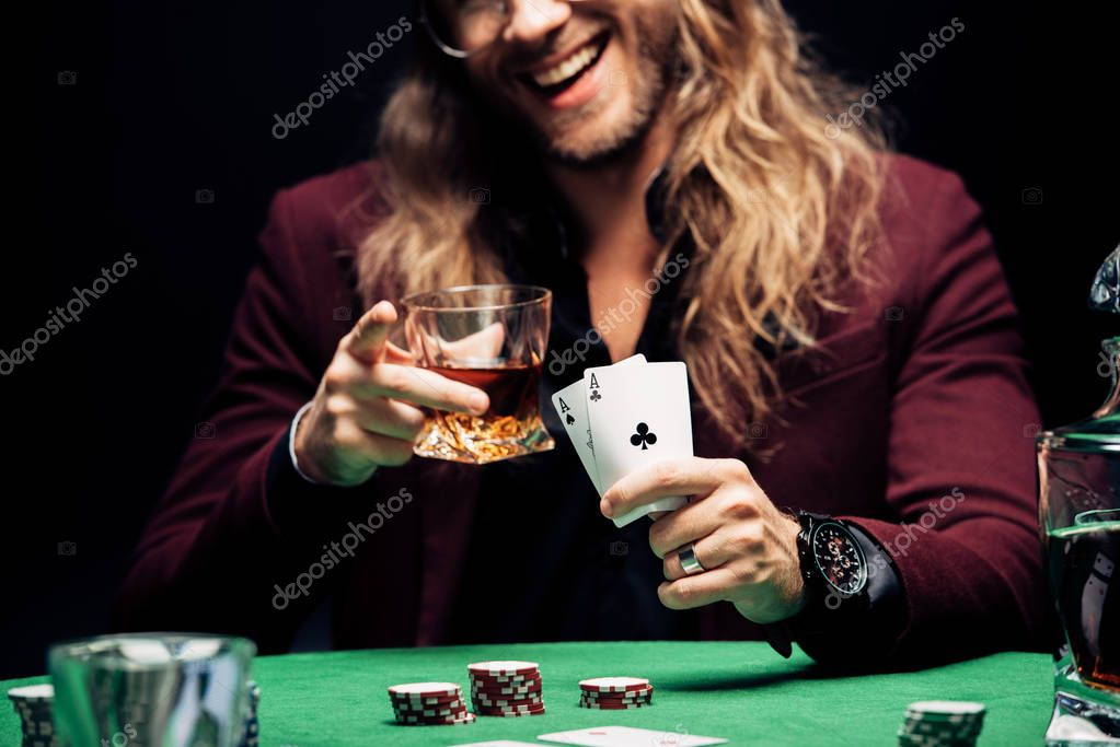 KYIV, UKRAINE - AUGUST 20, 2019: cropped view of happy man in eye glasses holding playing cards isolated on black