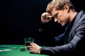 side view of frustrated man playing poker isolated on black
