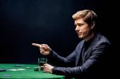 pohledný muž, ukazující prstem blízko pokrového stolu na černém