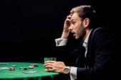 Kyjev, Ukrajina - 20. srpna 2019: boční pohled na překvapeného muže hrajícího poker u sklenice whisky izolované na černém
