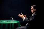 bello uomo gettando in chip di poker aria su nero