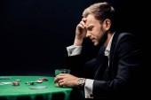Fotografia uomo frustrato tenendo vetro vicino tavolo da poker isolato sul nero