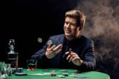 Fotografia uomo allegro gettando in chips di poker daria e sigaro su nero con fumo