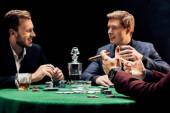 oříznutý pohled na člověka držící doutník poblíž přátel v pokeru na černém