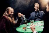 Fotografia vista ritagliata delluomo vicino amici felici vicino tavolo da poker su nero con fumo