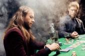 Kyiv, Ucraina - 20 agosto 2019: bei uomini che giocano a poker vicino al tavolo da poker con chip di poker e carte da gioco sul nero con fumo