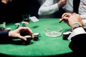 Fotografia vista ritagliato di uomo toccando chip di poker vicino croupier con carte da gioco isolate su nero